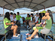 Staff and interns on fishing boat giving tour of fishing village
