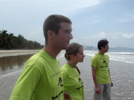 Volunteers and Chinese teacher looking out toward the ocean as released sea turtle swims away